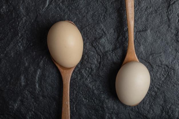 Due uova di gallina fresche su cucchiai di legno.