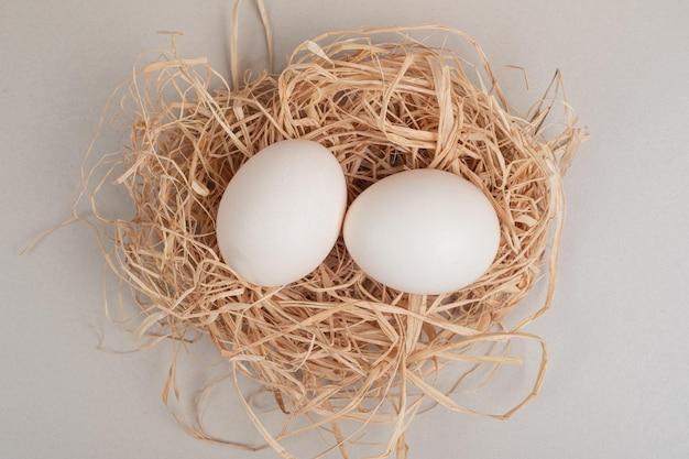 干し草に2つの新鮮な鶏の白い卵。