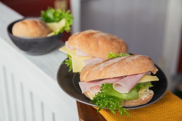 素朴な木製の背景にハム、チーズ、レタスの2つの新鮮なチャバタバゲットサンドイッチ。屋外のピクニックライフスタイル。