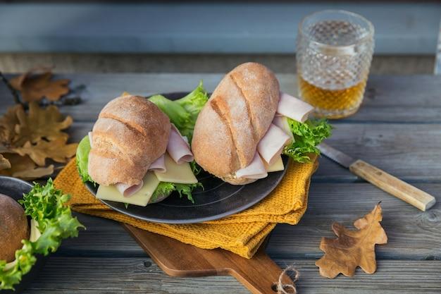 素朴な木製の背景にハム、チーズ、レタス、ビールのグラスと2つの新鮮なチャバタバゲットサンドイッチ。屋外の秋のピクニックライフスタイル。閉じる