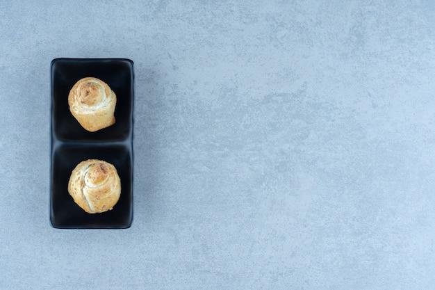 회색 배경 위에 검은 접시에 두 개의 신선한 쿠키.