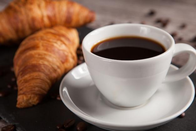 어두운 석재 테이블에 신선한 크루아상 두 개와 커피 한 잔. 맛있는 디저트.