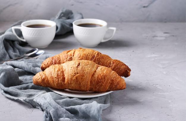 ライトグレーのコンクリートの背景に2つの焼きたてのクロワッサンと2杯のコーヒー。朝食または昼食のコンセプト。