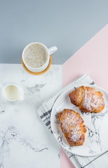 Two fresh croissants in a paper bag and cup of coffee on a tricolor background, top view