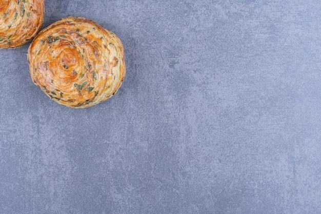 灰色の表面に2つの新鮮なおいしいペストリー