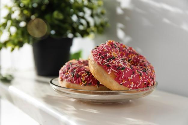 아침 햇살 아래 아침 식사 접시에 장식과 장식이 있는 신선한 도넛 2개.