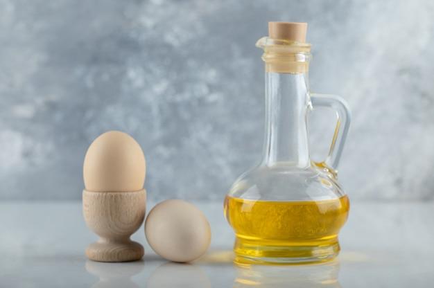 Due uova fresche in portauovo ea terra con una bottiglia di olio su sfondo bianco.