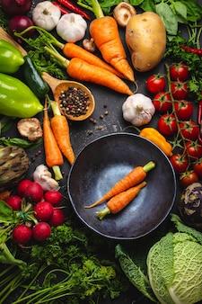 素朴な黒いコンクリートの背景にヴィンテージボウルと各種有機野菜の2つの新鮮な農場のニンジン。秋の収穫、ベジタリアン料理またはクリーンで健康的な食事のコンセプト、上面図