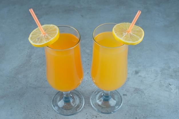 ストロー付きのガラスカップに入った2つのフレッシュフルーツジュース。