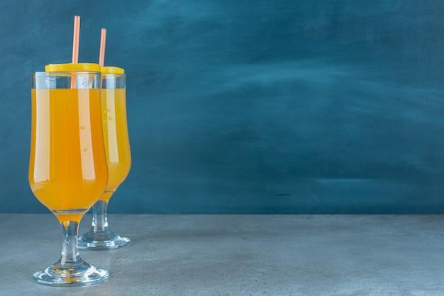 빨대와 함께 유리 컵에 두 개의 신선한 과일 주스.