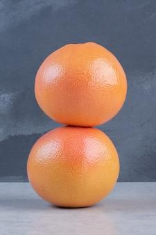 Два свежих грейпфрута на сером фоне.