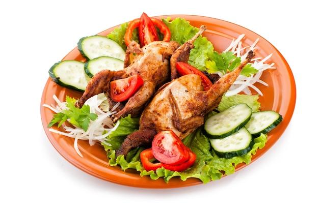 Два свежих жареных целых перепела с огурцом, сырыми помидорами и луком на тарелке с листовым салатом, изолированным на белом фоне