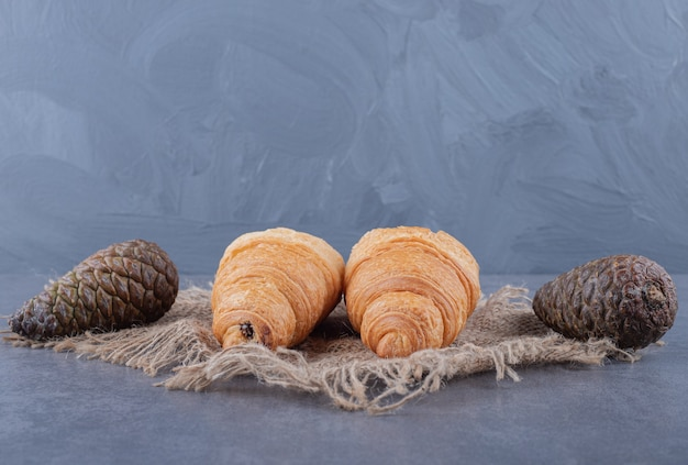 灰色の背景の上に2つの新鮮な自家製クロワッサンと松ぼっくり。