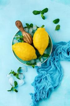 ターコイズ色のコンクリートの背景に青いプレートの2つの新鮮なレモン。食品の背景。上面図。