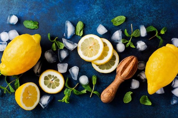 ターコイズ色のコンクリートの背景に濃い青のプレートで2つの新鮮なレモン。食品の背景。上面図。