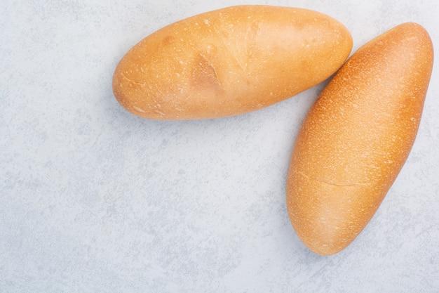 石の表面に2つの焼きたてのパン 無料写真