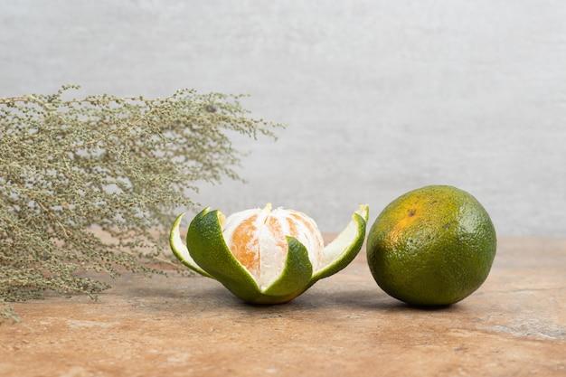 Due mandarini freschi su sfondo marmo.