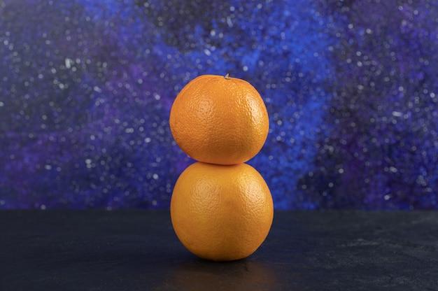 파란색 테이블에 두 개의 신선한 오렌지입니다.