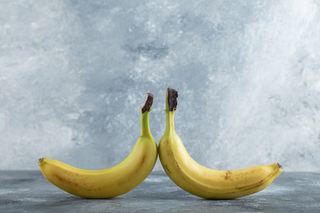 Due banane biologiche fresche su sfondo grigio fianco a fianco.