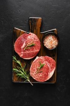 Two fresh parisienne raw steak on wooden board with salt, pepper and rosmary in a rustic style on old wooden background. black angus. top view.