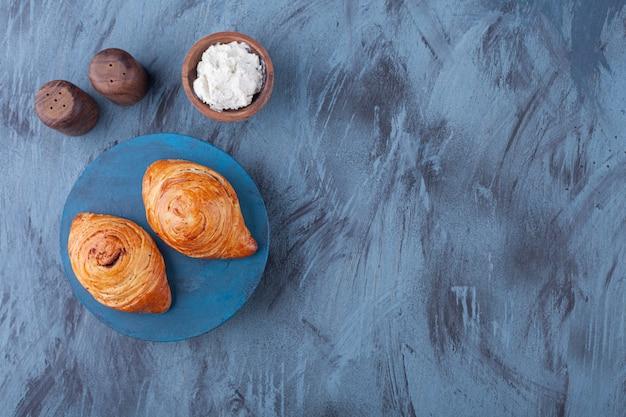블루 보드에 고기와 사워 크림으로 채워진 두 개의 신선한 파이.