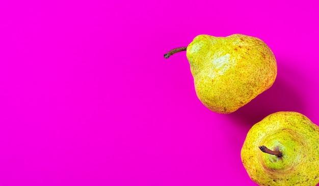 ピンクの紙の表面に2つの新鮮な梨