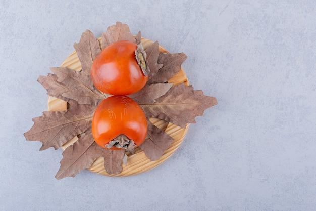 Due frutti di cachi freschi e foglie secche sul piatto di legno.