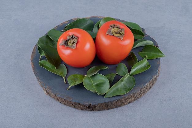灰色の木の板に葉を持つ2つの新鮮な柿