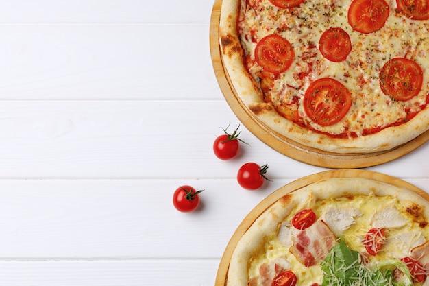 Две свежие пиццы на белом деревянном столе