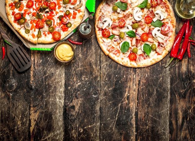 소스와 함께 두 개의 신선한 피자. 나무 배경에