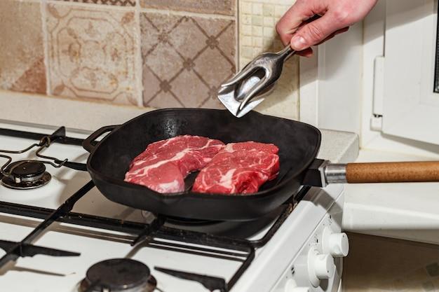 Два свежих сырых мяса стейка из говядины prime black angus chuck roll, обжаренные на сковороде на газовой плите.