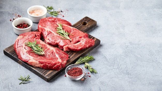 Два свежих сырых мяса prime black angus beef steaks, rib eye, denver, на деревянной разделочной доске.