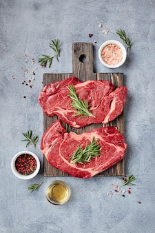Two fresh raw meat prime black angus beef steaks, rib eye, denver, on wooden cutting board. top view, place for text.