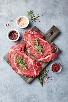 Two fresh raw meat prime black angus beef steaks, rib eye, denver, on wooden cutting board. top view