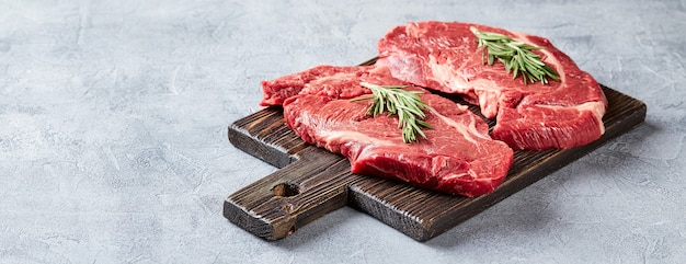 Two fresh raw meat prime black angus beef steaks, rib eye, denver, on wooden cutting board.