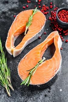 Два свежих сырых стейка из лосося с перцем и розмарином. черный фон. вид сверху.
