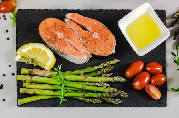 野菜とスパイスの2つの新鮮な生サーモンステーキ:アスパラガス、トマト、胡椒、ルッコラ、レモン、灰色の背景にオリーブオイル。健康食品ダイエットのコンセプトです。