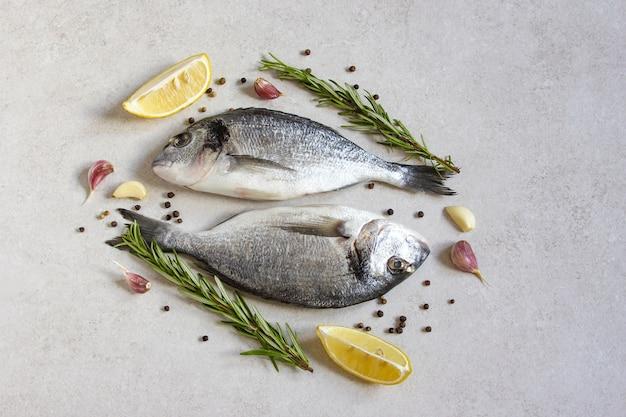 회색 배경에 향신료와 레몬을 넣은 신선한 생 바다 유기농 황새 또는 도미