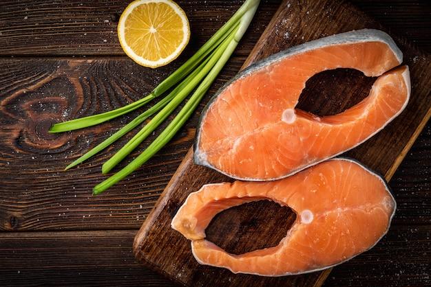 ダークウッドの背景に2つの新鮮な赤い魚のステーキ(サーモンまたはマス)。