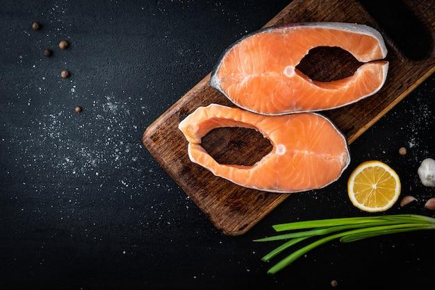 黒の背景にスパイスと木製のまな板に2つの新鮮な赤い魚のステーキ(サーモンまたはマス)。