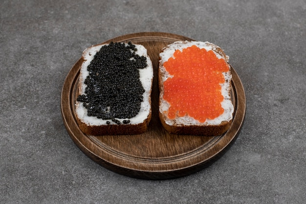 Two fresh sandwiches with caviar on wooden board over grey surface
