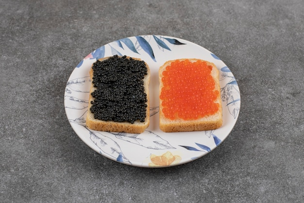 회색 표면 위에 접시에 빨간색과 검은색 캐비아를 넣은 신선한 샌드위치 2개