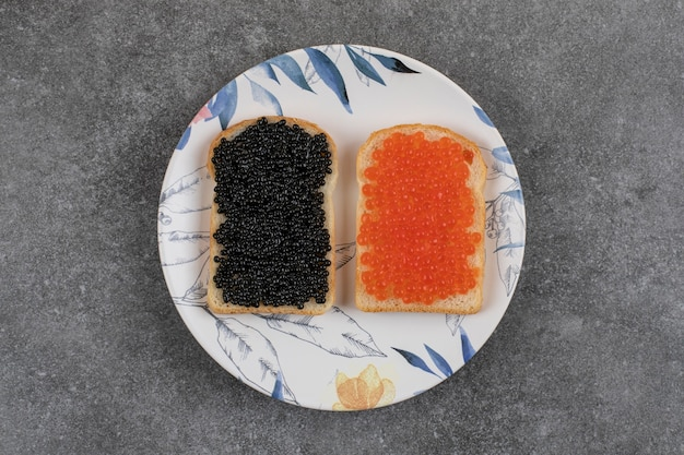 Two fresh sandwiches with red and black caviar on plate over grey surface.