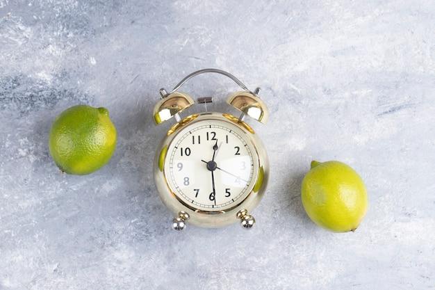 Два свежих кислых лимона с будильником на мраморе.