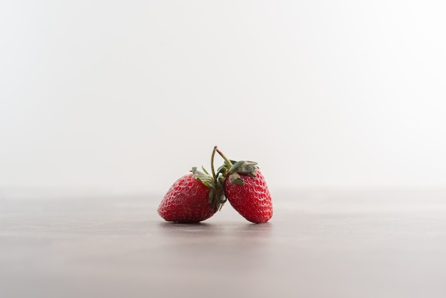 Two fresh strawberries on marble table.