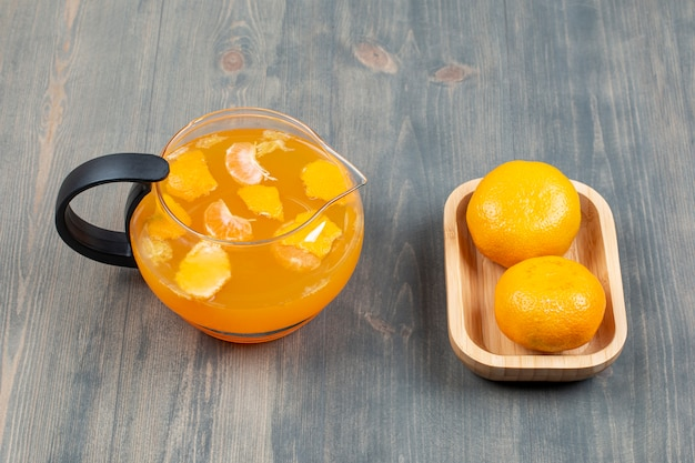 Два свежих мандарина со стеклянной банкой сока