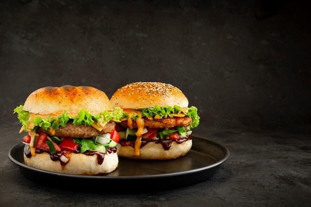Два свежих вкусных гамбургера на темном фоне