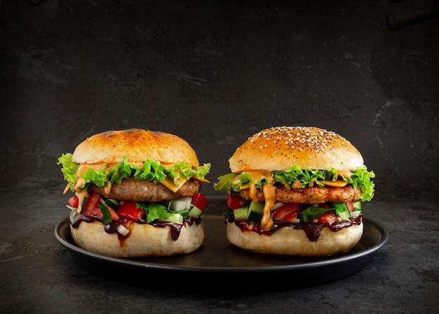 어두운 배경에 두 개의 신선한 맛있는 햄버거