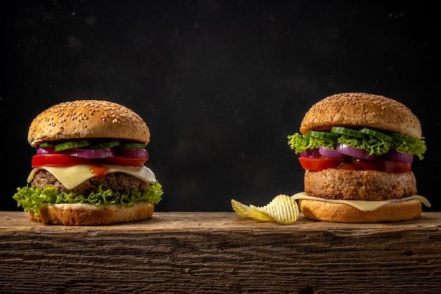 소박한 나무 테이블에 두 개의 신선한 맛있는 햄버거.