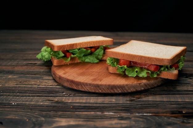 Два бутерброда со свежими помидорами на деревянной доске